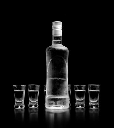 steamy: Close-up view of bottle and glasses of vodka standing isolated on black