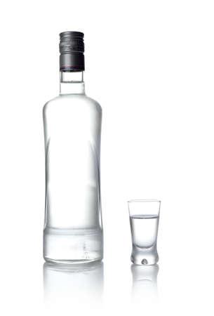 botella de licor: Vista de primer plano de la botella y el vidrio de pie de vodka aislado en blanco