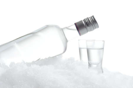 Close-up view of bottle lying on ice with two glasses of vodka on white background