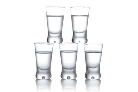Close-up view of many glasses of vodka standing on each other isolated on white photo