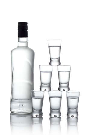 Close-up view bottle of vodka and many glasses of vodka standing on each other isolated on white photo