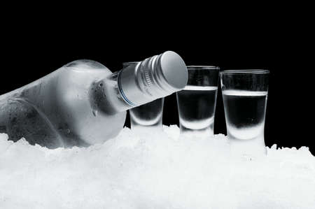 Close-up view of bottle of vodka with glasses standing on ice on black
