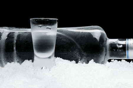cropped shots: Studio shot of bottle with glass of vodka lying on ice on black background