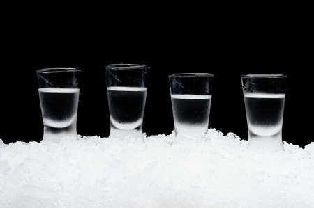 Close-up view of glasses of vodka on ice on black background Stock Photo