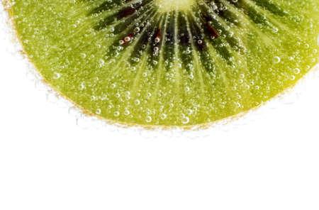 exotic gleam: Photo of sliced kiwi with water drop illuminated white light as background