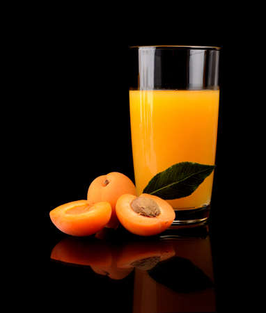 Studio shot of sliced orange apricot with leaf and apricot juice isolated on a black background photo