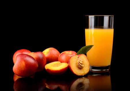Studio shot of sliced orange nectarines with leaf and nectarine juice isolated on a black background photo