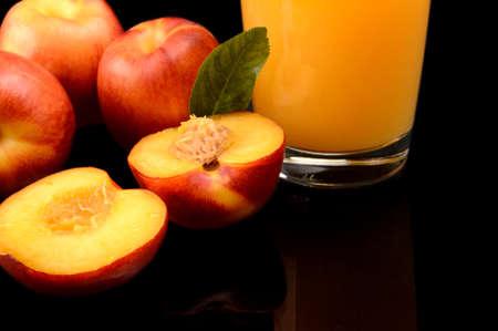 Studio shot of sliced orange nectarines with leaf and juice isolated on a black background photo