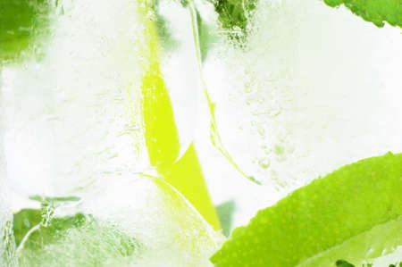 Photo of icy background with close up macro view od drink with ice cubes, mint and limes photo