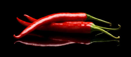 Studio shot of group of red chilli peppers isolated on a black background Stock Photo