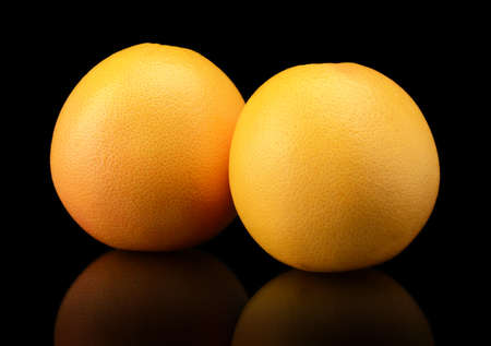 dyad: Two grapefruits isolated on black background