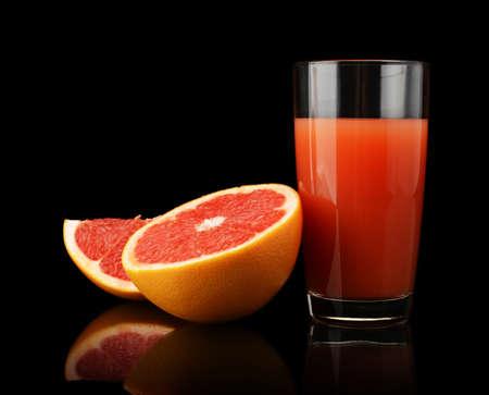 Studio shot of sliced three grapefruits with grapefruit juice isolated black background photo