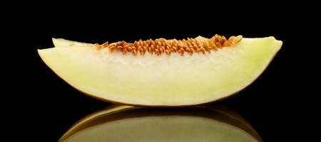 thou: Studio shot of slice of yellow canary melon isolated on black background Stock Photo