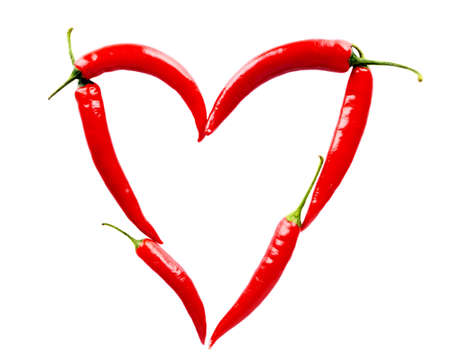 Heart made of red chili peppers isolated on white photo