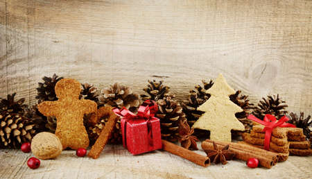 Christmas various gingerbread cookies with red gift, christmas tree, santa claus, stick scene on wooden surface photo