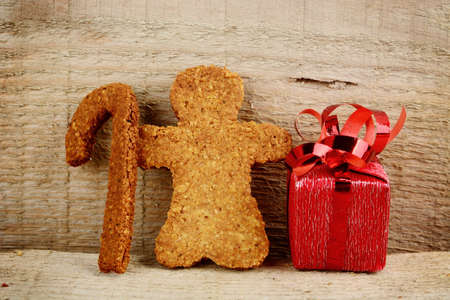 Christmas gingerbread cookies santa claus with gift on wooden surface photo