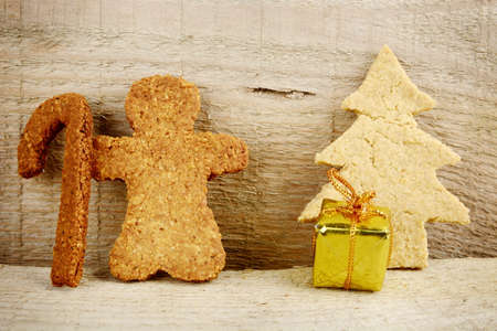 Christmas gingerbread cookies santa claus with gift under christmas tree on wooden surface photo