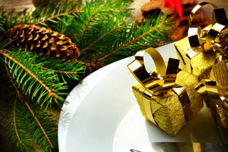 Closeup shot decorate christmas plate with golden gifts and pines on wooden surface photo