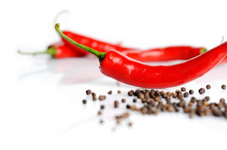 hottest: view of spicy chilli pepper and black peppers on a white background Stock Photo