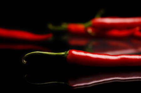 india food: Studio shot of spicy chilli peppers on black background