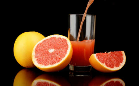 Studio shot of sliced grapefruits with grapefruit with poured juice isolated black background photo