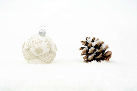 gewgaw: Single decoration of white christmas bauble and pine cone on snow isolated on white background