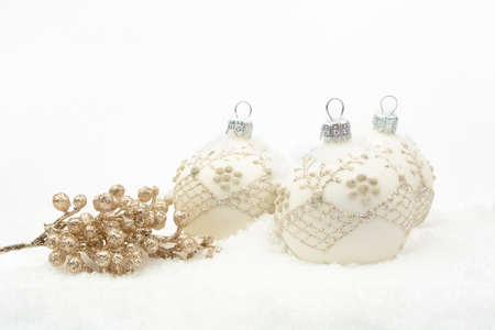 gewgaw: Decoration of white christmas baubles with gold decoration on snow on white background