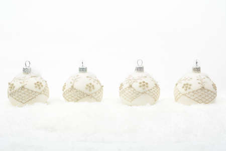 gewgaw: Decoration of white christmas baubles on snow on white background Stock Photo