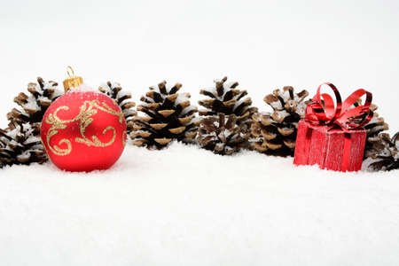 gewgaw: Decoration of red christmas baubles and pine cones on snow on white background