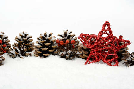 christmas ornamentation: Decoration of red star and pine cones on snow on white background Stock Photo