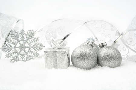 blithe: Decoraci�n de piedras de Navidad de plata y regalos con la cinta en la nieve en el fondo blanco