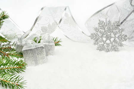 blithe: Decoration of silver christmas gifts,ribbon on snow with christmas tree branch on white
