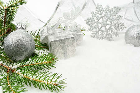 gewgaw: Decoration of silver christmas gifts,ribbon on snow with christmas tree branch on white
