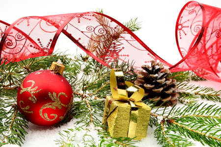 gewgaw: Decoration of gold christmas gifts,red ribbon and bauble on snow with pine cones, christmas tree branch on white Stock Photo
