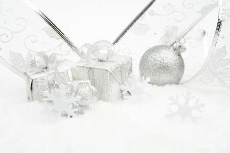 gewgaw: Decoration of silver christmas baubles and gifts with ribbon on snow on white background