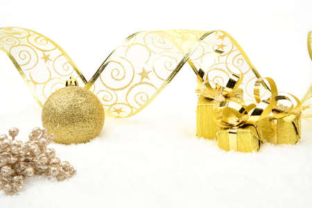 gewgaw: Decoration of golden christmas gifts,baubles,ribbon on snow on white