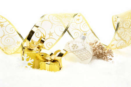 gewgaw: Decoration of golden christmas gifts,white bauble,ribbon on snow on white