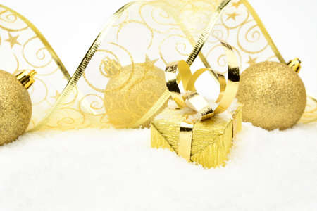 blithe: Decoration of golden christmas gifts,baubles,ribbon on snow withon white
