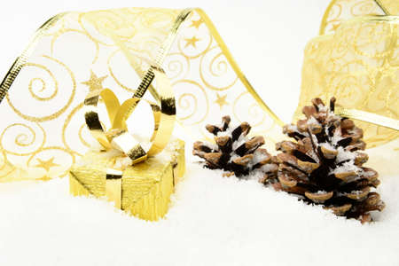 gewgaw: Decoration of golden christmas gifts with ribbon and pine cones on snow