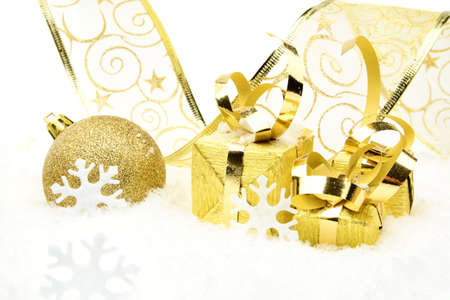 gewgaw: Decoration of golden christmas bauble and gifts with ribbon on snow on white background
