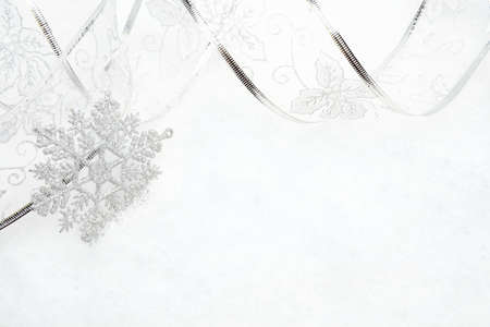 gewgaw: Decoration of silver christmas snowflake with ribbon on snow