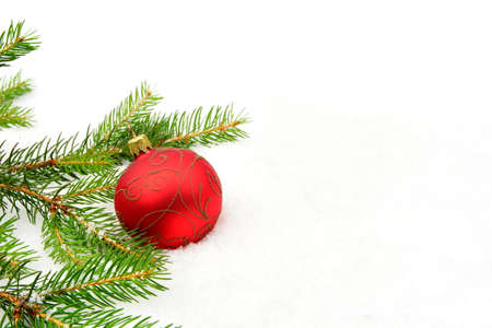 Decoration of red christmas bauble on snow, christmas tree branch on white photo