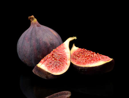 quarters: One whole fig and two quarters of figs isolated on black background