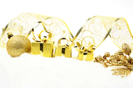 Decoration of golden christmas gifts,bauble,ribbon on snow on white photo
