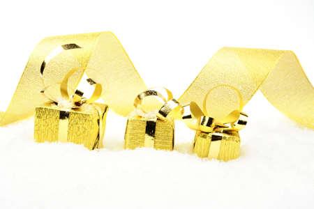 blithe: Decoraci�n de regalos de oro de la Navidad con la cinta en la nieve en el fondo blanco