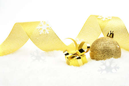 gewgaw: Decoration of golden christmas gift with ribbon on snow on white background Stock Photo