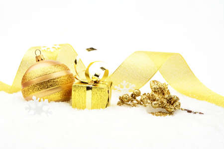 Decoration of golden christmas gift,bauble,ribbon on snow on white photo