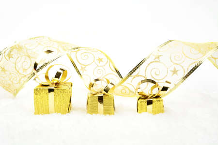 gewgaw: Decoration of golden christmas gifts with ribbon on snow on white background