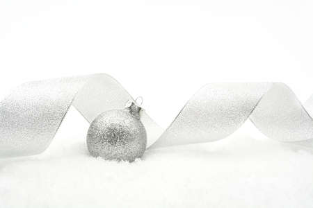 gewgaw: Decoration of Silver glitter bauble with ribbon on snow on white background Stock Photo