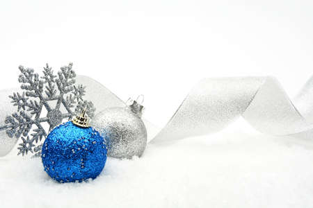 silver ribbon: Decoration of silver and blue glitter baubles with ribbon and snowflake on snow on white background